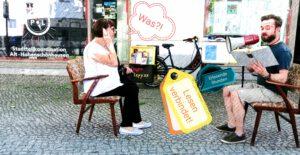 Eine Frau und Tomas Potyka sitzen sich auf Stühlen gegenüber und lesen sich vor