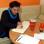 eine Frau schreibt ins Gästebuch