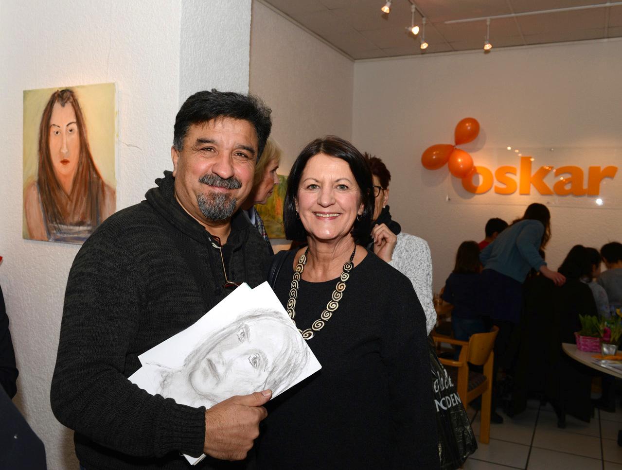ein Mann steht neben einer Frau und hält eine Zeichnung