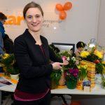rinr Frau zeigt auf einen Tisch mit Blumen und Geschenken