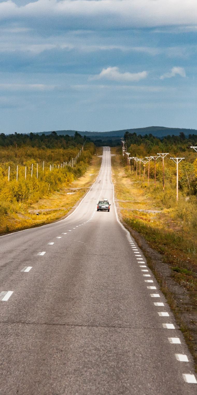Landschaft mit Straße und einem kleinen Auto