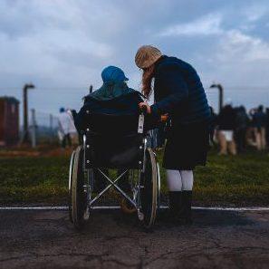 Zwei Menschen von hinten im Gespräch, einer im Rollstuhl, der andere gebeugt stehend daneben