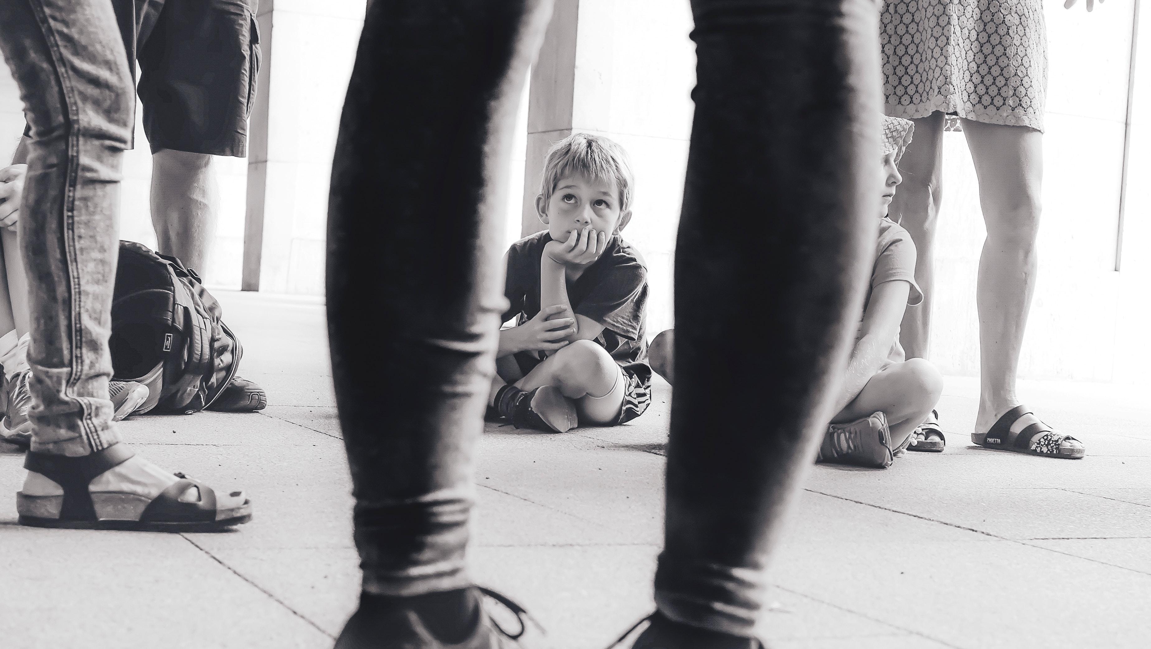 Sitzendes Kind blickt auf zu Umstehenden